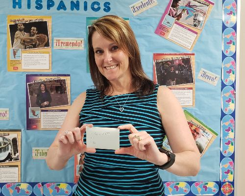 Mrs. Smith holding a gift card in front of a decorated bulletin board