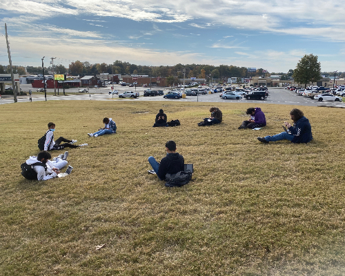 Circle of students sit on grass.