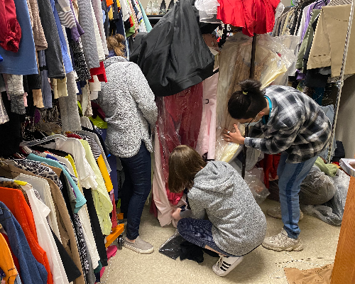 Three students organizing a closet full of hanging clothing.